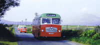 1966 - Convoy of MacBraynes buses travelling through Breakish with Beinn na Caillich ringed in mist